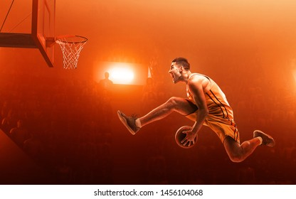 Basketball player in action on professional court. Slam dunk. Red background. Scattered light