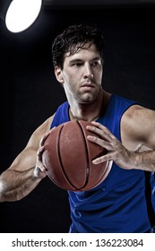 Basketball player with a ball in his hands and a Blue uniform. photography studio.
