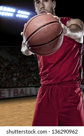 Basketball player with a ball in his hands and a red uniform. photography studio.