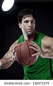 Basketball player with a ball in his hands and a green uniform. photography studio.