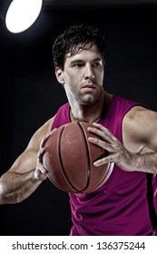 Basketball player with a ball in his hands and a pink uniform. photography studio.