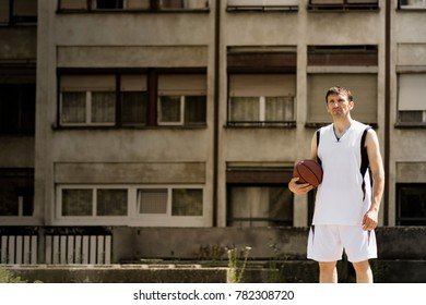 The basketball player with ball is standing at the street on building exterior background.