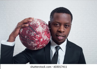 Basketball player with a ball. Successful young african sportsman in business suit.