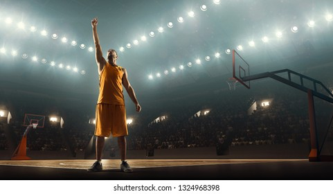Basketball player celebrates victory on a floodlit professional basketball court