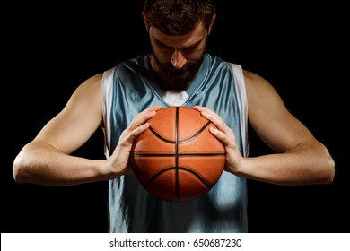 Basketball player concentrating on game. Young bearded man in blue tank top holding a ball with both hands on black background.
