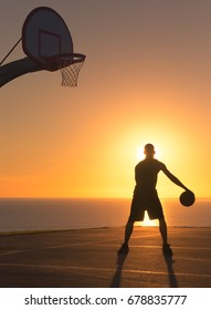 Basketball player dribbling a ball at sunset. Silhouette