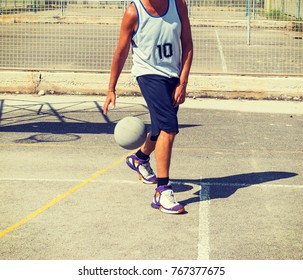 Basketball player dribbling betweeen the legs in a playground