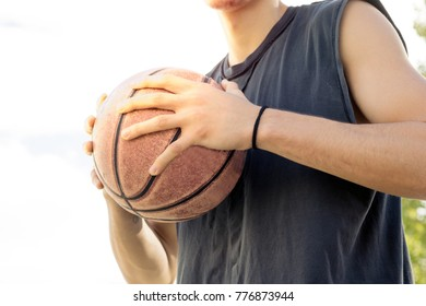 basketball player holding a ball close up mid-section