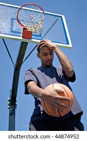 Basketball player holding his head in disappointment over losing the game.
