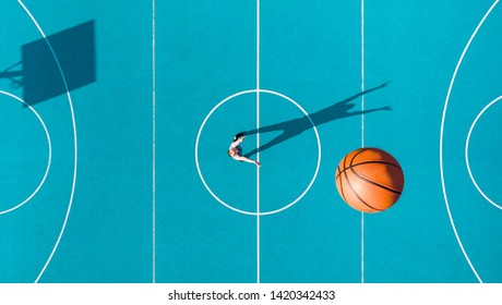 Basketball Player, Long Shadows on Basketball Court, Creative Visual Art, Aerial Image.