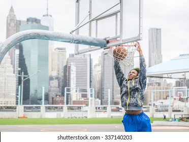 Basketball player making a slam dunk. New york background