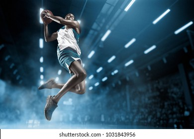 Basketball player in motion or movement on big professional arena during the game. Player making slam dunk. unbranded uniform. attack and decisive blow concept. professorial afro american athlete