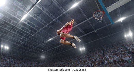 Basketball player on big professional arena during the game. Basketball player makes slum dunk. Player wears unbranded clothes.