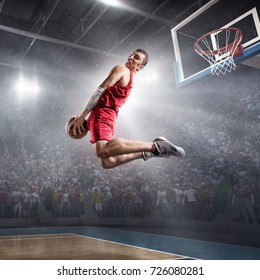 Basketball player on big professional arena during the game. Basketball player makes slam dunk. Player wears unbranded clothes.