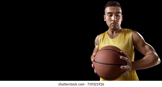 Basketball player on a black background. Isolated basketball player in unbranded clothes. Basketball player prepares to throw the ball.