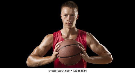 Basketball player on a black background. Isolated basketball players in unbranded clothes. Player hold a ball.