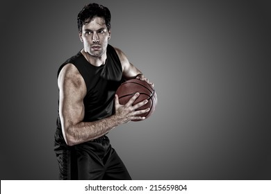 Basketball player on a  black uniform, on a black background.