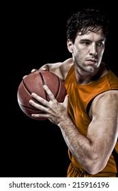 Basketball player on a  orange uniform, on a black background.