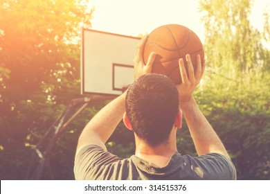 Basketball player on a outdoor court.