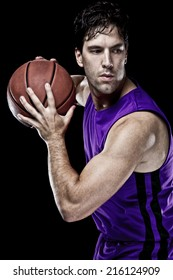 Basketball player on a  purple uniform, on a black background.