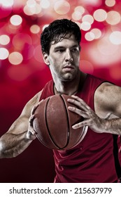 Basketball player on a  red uniform, on a red lights background.