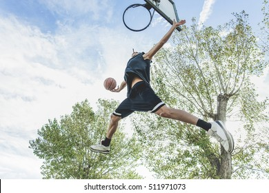 Basketball player performing huge slam dunk on the court in urban grunge camp with back light - Young athlete in action outdoor - Sport concept - Original sunlight - Soft warm filter