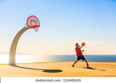 Basketball Player playing streetball. Beautiful sunrise background.