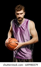 Basketball player posing with ball over black background. Muscular and fierce man holding a ball looking straight at the camera.