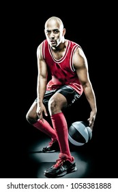 Basketball player in red trikot with ball over black background