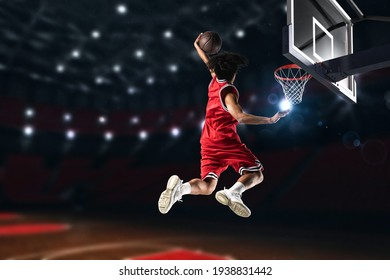 Basketball player in red uniform jumping high to make a slam dunk to the basket