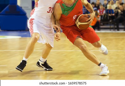 A basketball player runs across the court and holds a basketball in his left hand