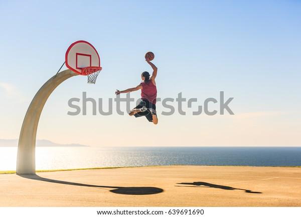 Basketball Player scoring an amazing slam dunk outdoors.
