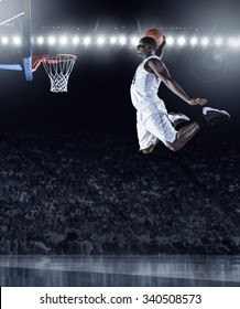 Basketball Player scoring an athletic, amazing slam dunk in a professional basketball game