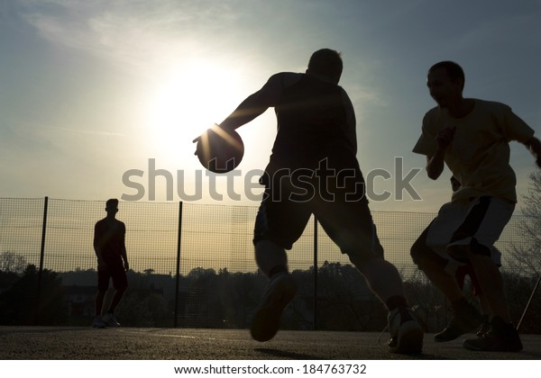 Basketball player silhouettes playing on an outdoor court as the sun creates a flare by the ball