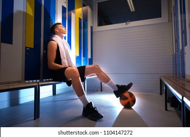 Basketball player sitting in the locker room.