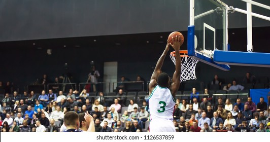 A basketball player throws a ball into the hoop. In the background, the fans are sitting in the stands