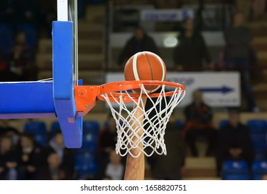 A basketball player throws the ball into the basket with one hand. Fans sit on the stands in the background