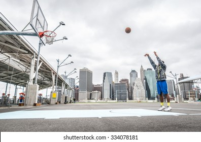 Basketball player training shots on the court. New york background and Manhattan buildings