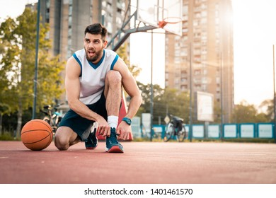 Basketball player tying shoelace for game at basketball court outdoors. Getting ready to play sport. Urban background at sunset.