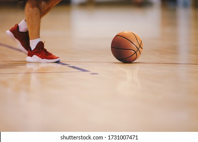 Basketball player walking on wooden court. Basketball over the floor. Basketball sports court