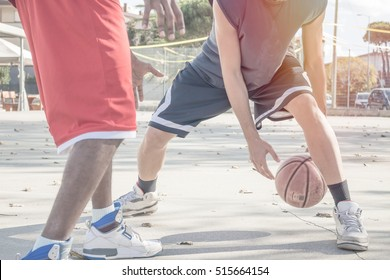 basketball players in action on a sunny day in open court. african american guys playing basketball together. close up shot with motion blur on bouncing ball