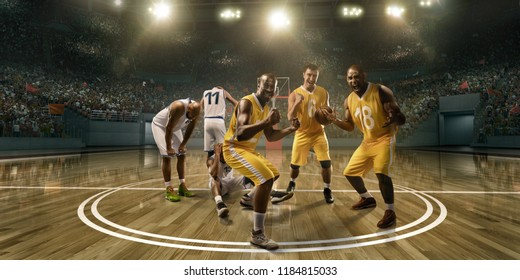 Basketball players emotionally rejoice at victory on professional basketball stadium. Players from opposing teams are sad because of the defeat