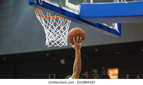 A basketball player's hand throws the ball into the hoop