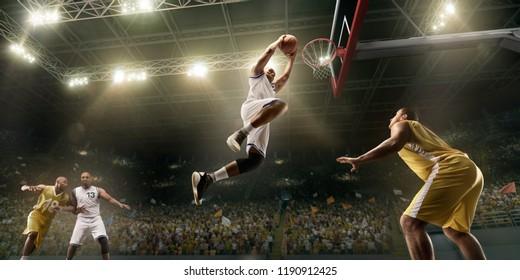 Basketball players on big professional arena during the game. Basketball player makes slum dunk. Bottom view