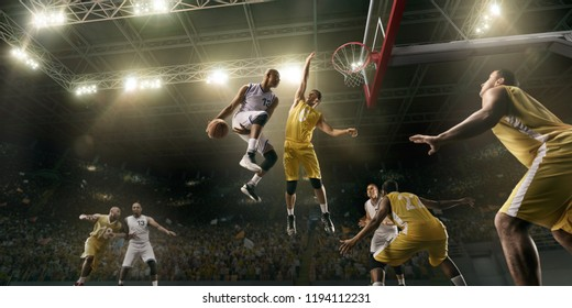 Basketball players on big professional arena during the game. Basketball player makes slum dunk