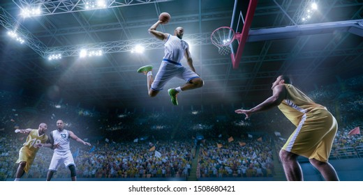 Basketball players on big professional arena during the game. Basketball player makes slam dunk. Bottom view