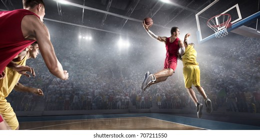 Basketball players on big professional arena during the game. Players fight for the ball. They are wearing unbrand clothes.