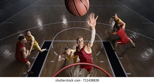 Basketball players on big professional arena during the game. Basketball players makes slum dunk. Players are wearing unbranded clothes.