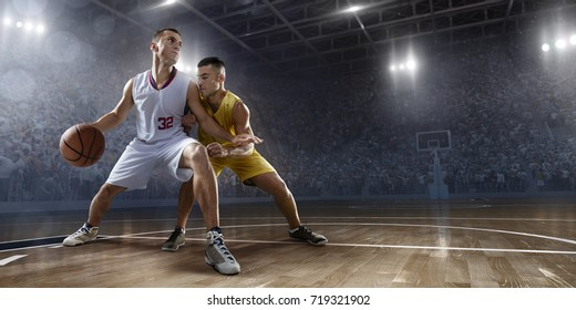 Basketball players on big professional arena during the game. Players fight for the ball. Players wearing unbranded clothes.