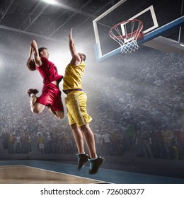 Basketball players on big professional arena during the game. Basketball player makes slam dunk. Players wears unbranded clothes.